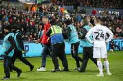 Three fans arrested after pitch invasions during Swansea City's FA Cup tie against Man City