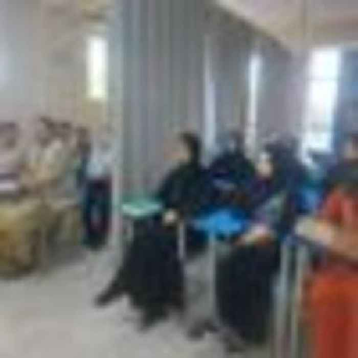 Male and female students segregated by curtain as university studies resume in Afghanistan