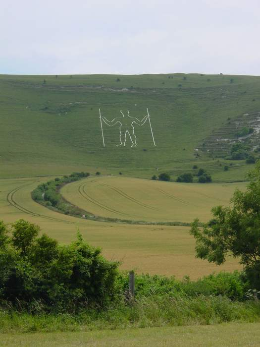 Giant Long Man carving given face mask