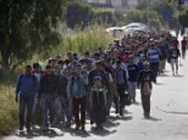 The march of the migrants: Hundreds of Syrians and Afghans walk through Kos as 1,200 migrants arrive on Greek islands in just two days