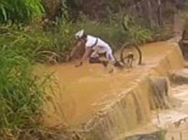 Brazilian cyclist plunges into muddy water while trying to cross fast-flowing river