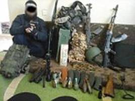 The 'ISIS terrorist claiming to be a Syrian refugee': Shocking image shows fanatic posing with cache of weapons and ammunition before being arrested at German shelter for asylum seekers
