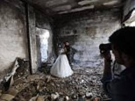 Syrian newlyweds pose for wedding photographs among the ruins of Homs