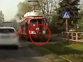 horrifying moment a woman is hit by tram and sucked under the carriage after walking blindly across the tracks - but she miraculously survived