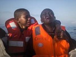 distressing moment a ten-year-old boy tries to comfort his sister, 11, as they are rescued from an overcrowded migrant boat while trying to reach italy