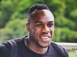michail antonio is all smiles on his first day at st.george's park as he walks through the door with west ham bags