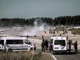 The Battle of Calais: Police use tear gas to repel 300 migrants as they try to storm a road leading to the French port