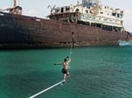 water way to show off: daredevils tie slackline to a shipwreck and cross the ocean
