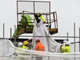 statue of the queen mother is lowered in the centre of prince charles' poundbury estate