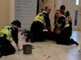 Dramatic moment three police officers tackle a suspect and pin him to the ground sending £50 notes and coins flying through the air as stunned bank customers watch on