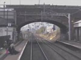 Heart-stopping moment a young girl pulls her friend from railway tracks as a 100mph train speeds towards her with just seconds to spare