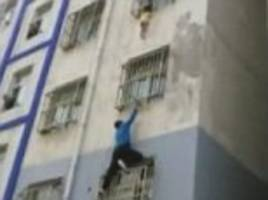 heroic moment a real-life 'spider-man' scales building with his bare hands to save toddler who is dangling from a window after getting his neck trapped between bars