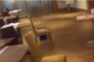 tables and chairs crash across a restaurant as weather causes...
