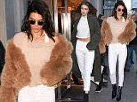 kendall jenner and gigi hadid rock matching white jeans as they hit the shops in paris