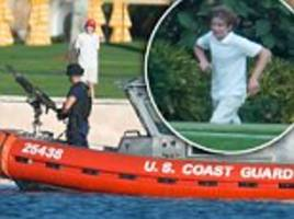 barron trump is surrounded by heavily-armed guards as he plays at mar-a-lago