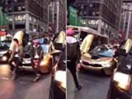 sweet justice? prankster stops traffic to stage 'photoshoot' on a new york city street, but is swiftly brought to a halt by furious motorist who smashes his luxury car with a baseball bat