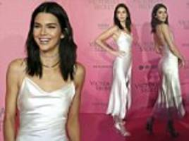 A vision in white! Kendall Jenner displays her toned figure in a slinky silk slip dress as she celebrates Victoria's Secret Fashion Show in Paris