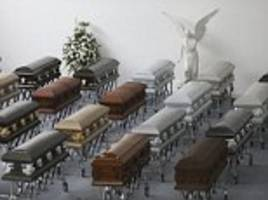 united for one last time: coffins containing the remains of the brazilian footballers killed in colombian plane disaster are laid out side by side in funeral home