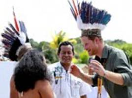 that's bound to ruffle a few feathers! prince harry sports a traditional headdress as he meets dancers in guyana on the penultimate day of his caribbean tour