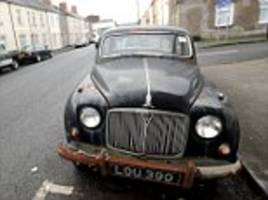 long term parking: rusty car that has not moved for a decade despite being fully taxed and insured becomes a local landmark