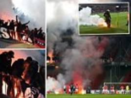 Ajax's Europa League tie at Standard Liege marred by crowd trouble as away fans launch flares onto the pitch