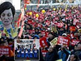 thousands of protestors carry effigies of the south korean president and floats depicting her in jail as they demand her resignation