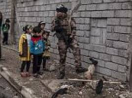 half-buried with his legs in the air... and left for children to stare and giggle at: isis fighter killed in mosul becomes macabre display in reclaimed city