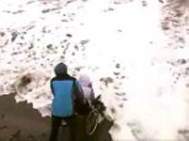 Unbelievable! Carer takes disabled patients in a wheelchair up to the water's edge in his WHEELCHAIR despite 14 death warnings of a storm surge on the coast