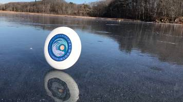 frisbee glides along frozen lake like an olympic ice skater; video