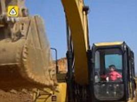 boy operates digger after learning from his father