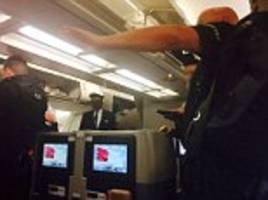 security expert wrestles and handcuffs a rowdy passenger