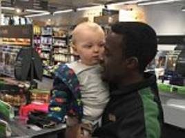 m&s worker holds restless baby for mother as he works
