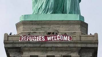 'Refugees Welcome' banner hung on Statue of Liberty in New York