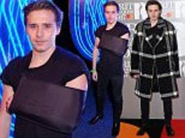 Brooklyn Beckham shows off arm sling at BRITs after party