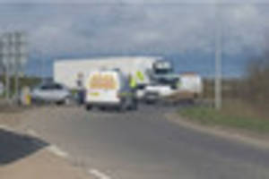 firefighters cut person from wreckage after lorry and car smash...