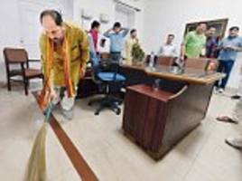 up minister picks up broom, cleans office