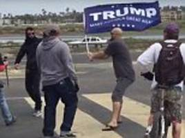 Trump supporter hits anti-fascist protester with MAGA flag