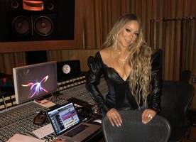 mariah carey's boobs almost pop out of her plunging black top