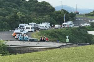 a group of travellers have pulled up in their caravans in a popular swansea bay car park