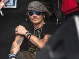 Johnny Depp dodges the festival pong with Azzi Glasser