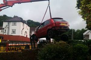 a woman heard a bang and found this car destroyed in her front garden