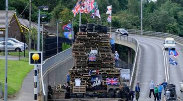 Talks avert repeat of bonfire at Northern Ireland flyover fail as youths pile up material