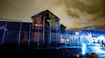 belfast trouble: credit union building torched in divis just hours after cars are set ablaze in markets area