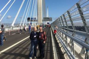 like wind filling a ship's sails thumbs up from crieff couple walking over new queensferry crossing