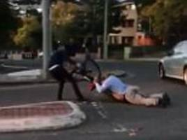 Moment cyclist drags a driver across a road on his stomach