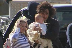 poldark star aidan turner pictured cuddling cute baby on holywell bay set in newquay