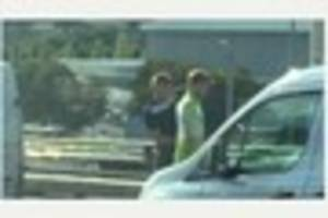 dartford tunnel traffic: man passes the time by wrapping friend...