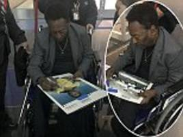 Brazil legend Pele pictured in a wheelchair at JFK Airport