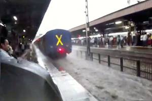 train speeds dangerously through flooded station, drenching commuters; video