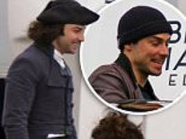 poldark's aidan turner covers up famous locks on set